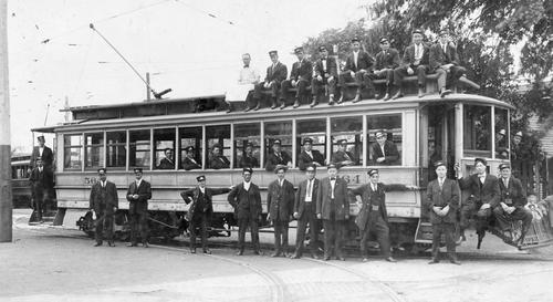 The photograph shows an electric trolley -- a part of Toledo's innovative urban transportation infrastructure, which started in 1884 and came to a halt in 1919. The staff of the trolley company proudly posing.