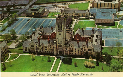 "Aerial View, University Hall of Toledo University. Printed caption reads, ""University Hall is the main building on the campus of the University of Toledo. Over 15,000 students attend day and evening classes at this state university."" A hand written note says, ""about 1970-72. Note barracks from World War II between U-Hall and Union bldg - to left of sidewalk. The wooden buildings were Gov. Surplus in 1945 and used for classrooms - Demolished Feb. 1972 - Parking lot now is Centennial Mall, dedicated Oct. 1980."""