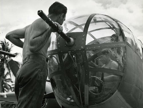 Marine aircrew adjust a .50-calibre machine gun in a North American Mitchell (B-25) before Marine Air operation out of Espiritu Sante in the Pacific [against Japanese forces]