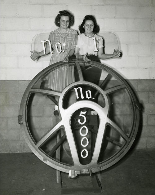 Two employees holding the nose to the 5000th B-29.  These safety glasses eventually made their way to postwar automobile production as windshields