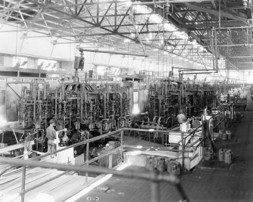 Bottle machines at the Charleston Plant.  The print might have been produced in reverse as the label on the bottom is reversed.  Digital imaging software can reverse this image