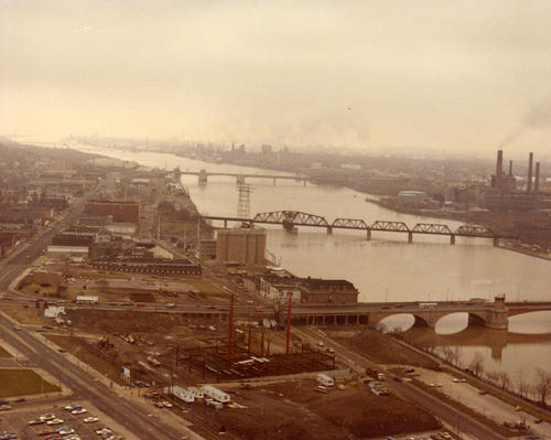 A view of the Owens-Illinois building during early stages of construction, with the Cherry Street bridge and Maumee river in the background.