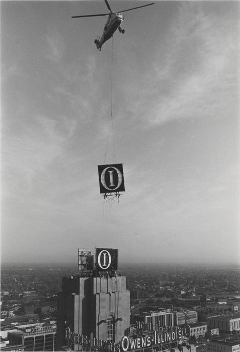 Picture of the helicopter removal of the O-I sign from atop the former headquarters at the Ohio Savings Bank and Trust building.
