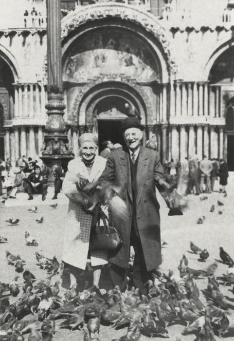 Picture of Ward and Miriam Canaday in Paris at Notre Dame surrounded by pigeons.