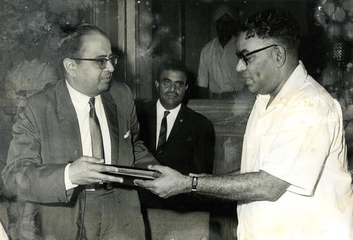 Dr. S. Chandrasekhar, Minister for Health and Family Planning, was presented in New Delhi on June 30, 1967 films and literature on family planning campaign by the Indian Society of Advertisers and the Advertising Agencies Association of India.  Photo shows Dr. S. Chandrasekhar receiving a packet of film and literature from Shri Arvind Mafatlal, Chairman Indian Society of Advertisers., This photograph and others in the same folder have been partially damaged.
